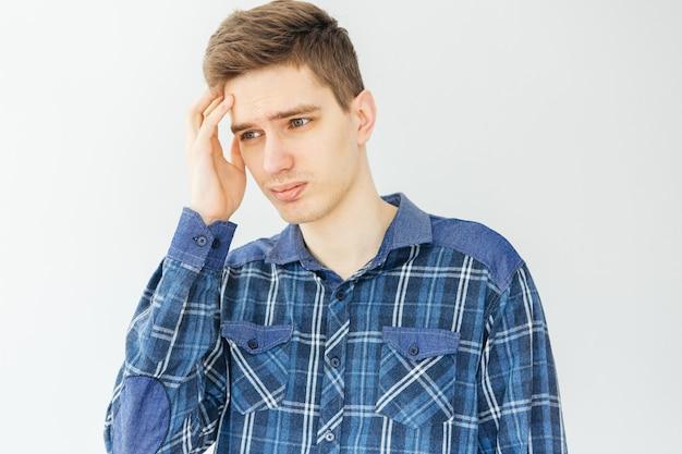 Smutny młody człowiek w niebieskiej koszuli na jasnoszarym tle. depresja, problemy i stres.