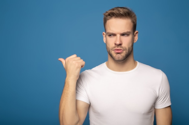 Smutny młody człowiek wskazuje z palcem backwards odizolowywającym na błękicie