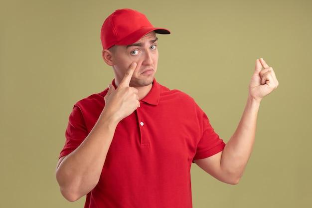 Smutny młody dostawca ubrany w mundur i czapkę, ściągając powieki, pokazując gest wskazujący na oliwkowej ścianie