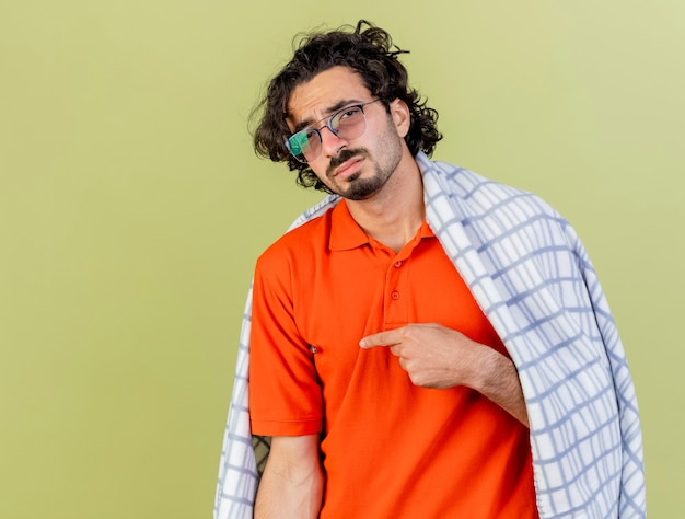 Smutny młody kaukaski chory człowiek w okularach zawinięte w kratę patrząc na kamery, wskazując na bok na białym tle na oliwkowym tle z miejsca na kopię