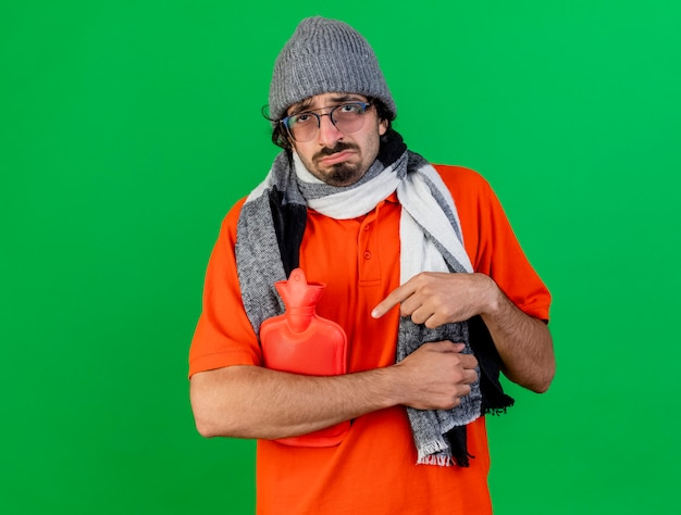 Smutny młody kaukaski chory mężczyzna w okularach czapka zimowa i szalik trzyma i wskazuje na torbę z gorącą wodą patrząc na kamerę odizolowaną na zielonym tle z miejscem na kopię