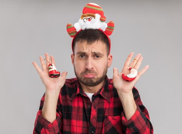 Smutny młody kaukaski mężczyzna ubrany w opaskę świętego mikołaja, trzymając santa claus ozdoby świąteczne patrząc na kamery na białym tle