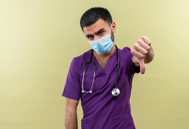 Smutny młody lekarz mężczyzna ubrany w fioletową odzież chirurga i maskę medyczną stetoskop kciuk w dół na odosobnionym zielonym tle