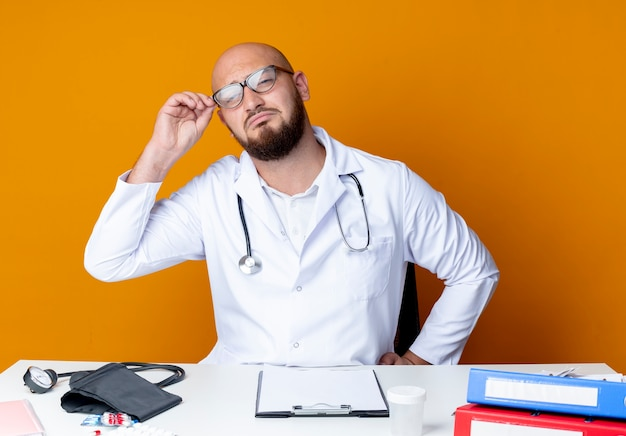 Smutny młody łysy lekarz mężczyzna ubrany w szlafrok i stetoskop siedzi przy biurku z narzędziami medycznymi na pomarańczowo okulary