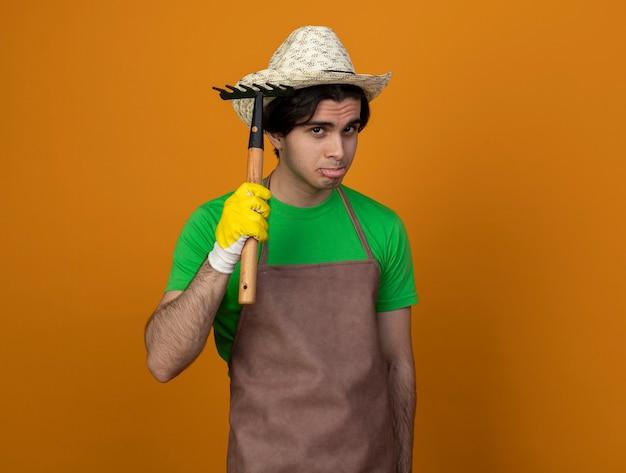 Smutny młody męski ogrodnik w mundurze na sobie kapelusz ogrodniczy z rękawiczkami podnosząc kapelusz z grabiami