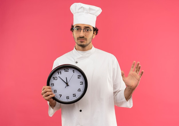 Smutny młody mężczyzna kucharz ubrany w mundur szefa kuchni i okulary, trzymając zegar ścienny i rozłożoną rękę na białym tle na różowej ścianie