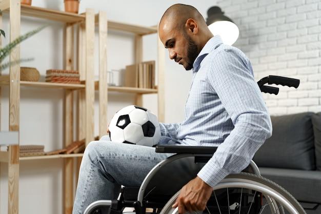 Smutny młody niepełnosprawny mężczyzna na wózku inwalidzkim, trzymający piłkę nożną