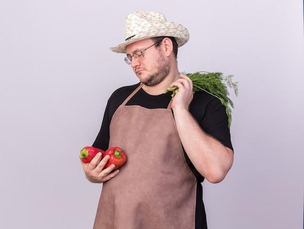 Smutny młody ogrodnik mężczyzna w kapeluszu ogrodnictwo gospodarstwa papryki z koperkiem na białym tle na białej ścianie