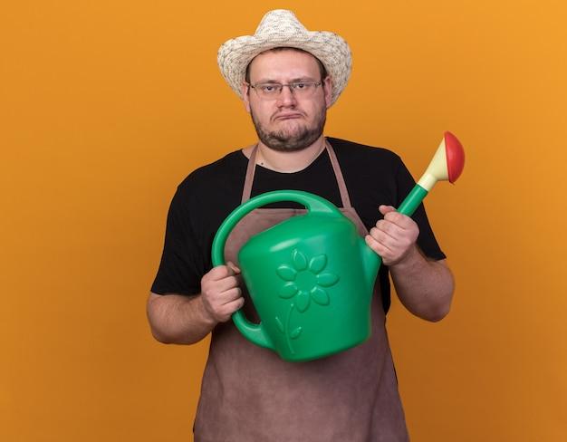 Smutny młody ogrodnik mężczyzna w kapeluszu ogrodnictwo trzymając konewkę na białym tle na pomarańczowej ścianie