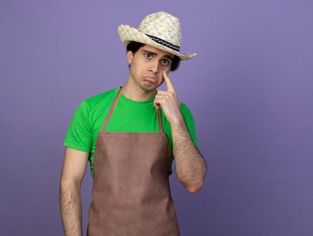 Smutny młody ogrodnik mężczyzna w mundurze na sobie kapelusz ogrodniczy kładąc palec na oku