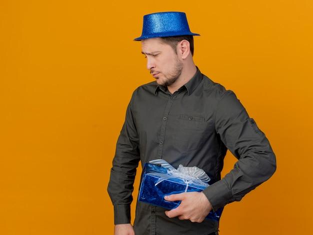 Smutny młody partyjny facet na sobie niebieski kapelusz gospodarstwa pudełko na białym tle na pomarańczowo