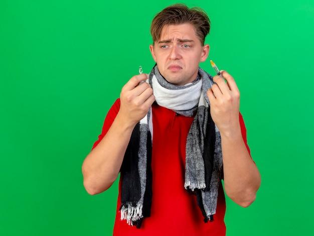 Smutny młody przystojny blondyn chory ubrany w szalik, trzymając strzykawkę i ampułkę medyczną, patrząc na ampułkę odizolowaną na zielonej ścianie z miejscem na kopię