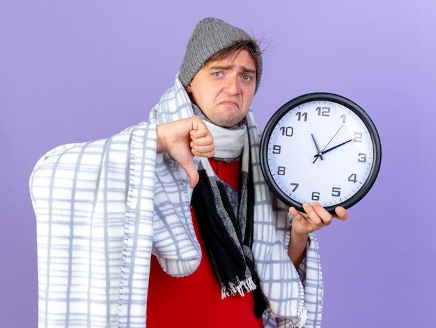 Smutny młody przystojny blondyn chory w czapce zimowej i szaliku owiniętym w kratę, trzymając zegar patrząc na kamerę, pokazując kciuk w dół na białym tle na fioletowym tle