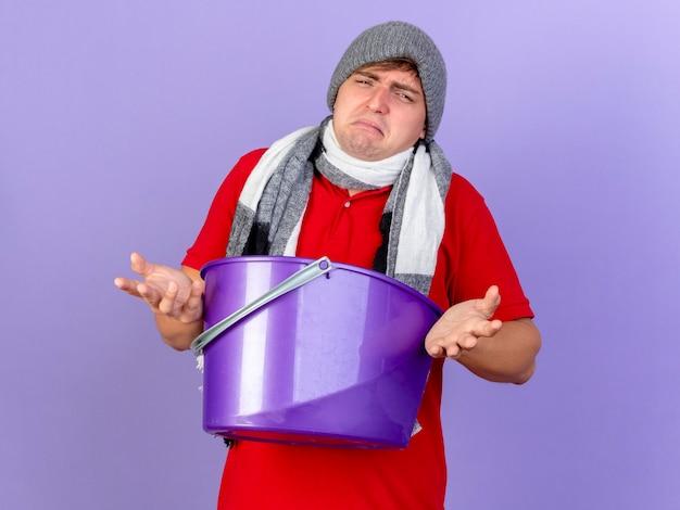 Smutny, młody przystojny blondyn chory w czapce zimowej i szaliku, trzymając plastikowe wiadro na białym tle na fioletowej ścianie