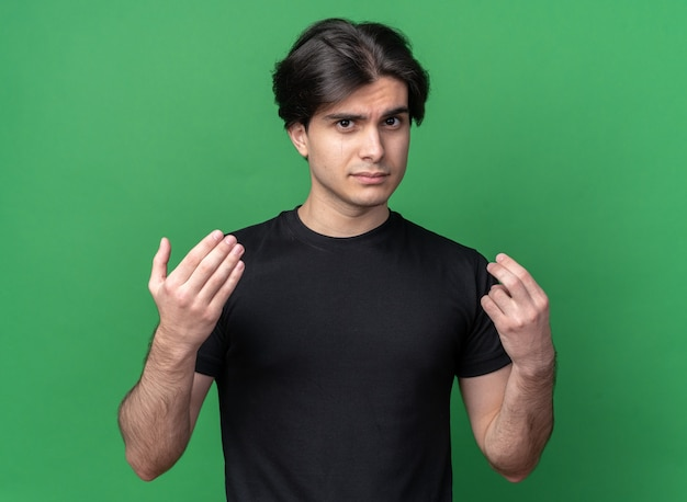 Smutny młody przystojny facet ubrany w czarną koszulkę pokazujący gest napiwku na zielonej ścianie