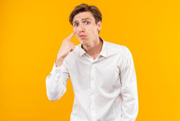 Smutny młody przystojny facet w białej koszuli, odciągając powiekę na pomarańczowej ścianie