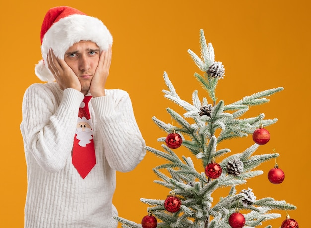 Smutny młody przystojny facet w świątecznej czapce i krawacie świętego mikołaja stojący w pobliżu udekorowanej choinki, trzymając ręce na twarzy, patrząc na kamerę odizolowaną na pomarańczowym tle