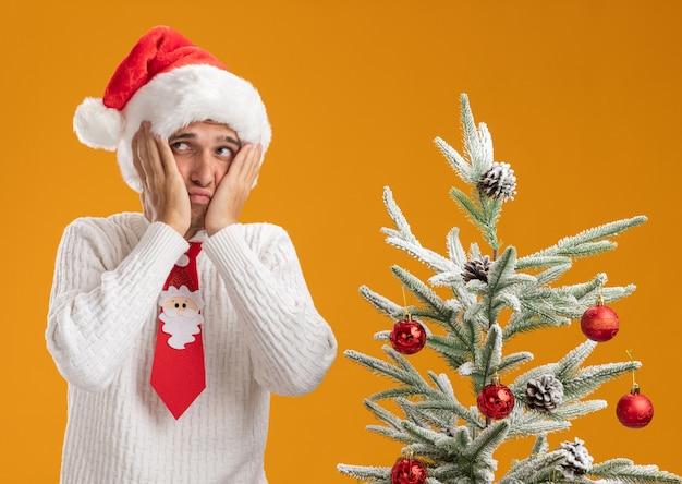 Smutny młody przystojny facet w świątecznej czapce i krawacie świętego mikołaja stojący w pobliżu udekorowanej choinki trzymając ręce na twarzy patrząc z boku na białym tle na pomarańczowym tle