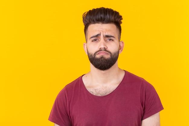 Smutny młody przystojny mężczyzna hipster z brodą w bordowej koszulce pozuje na żółtym tle