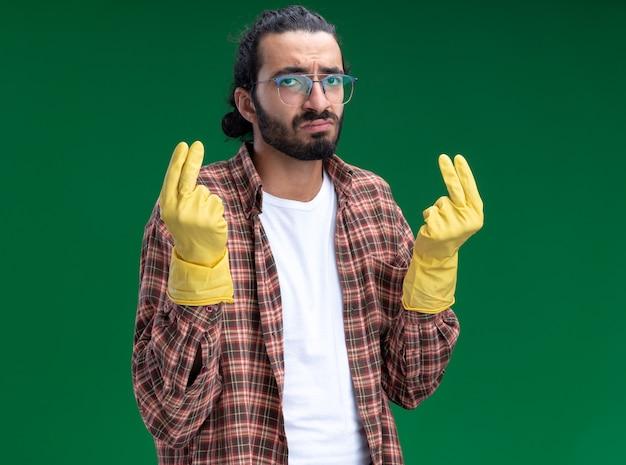 Smutny, młody przystojny sprzątacz sobie t-shirt i rękawiczki pokazując gest końcówki na białym tle na zielonej ścianie