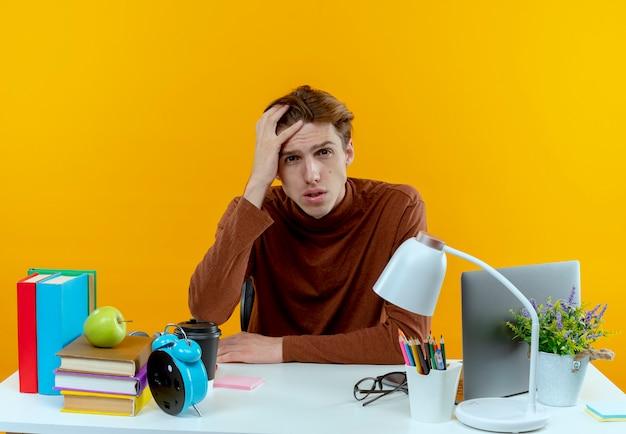 Smutny młody uczeń chłopiec siedzi przy biurku z narzędziami szkolnymi kładąc rękę na głowie na białym tle na żółtej ścianie