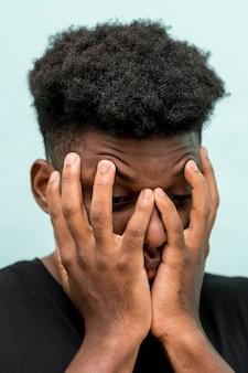 Smutny murzyn z rękami zakrywającymi twarz