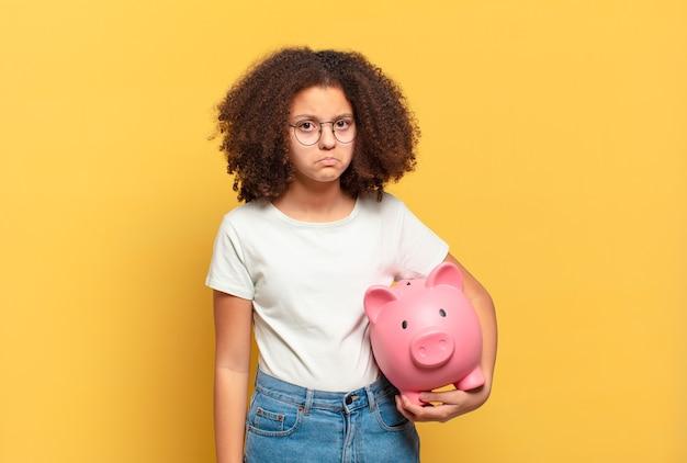 Smutny nastolatek afro z skarbonka. koncepcja oszczędności