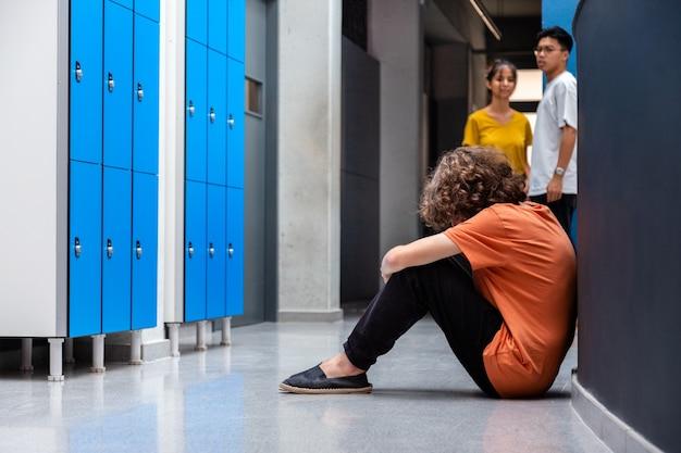 Smutny nastolatek rasy kaukaskiej siedzi na podłodze na korytarzu szkoły, podczas gdy jego koledzy z klasy go obserwują. skopiuj miejsce. koncepcja nękania konsekwencji. depresja młodzieńcza