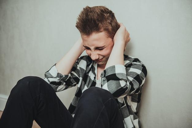 Smutny nastolatek siedzi na podłodze myśląc o swoich kłopotach i nieszczęśliwym życiu i zamyka uszy, aby rozwiązać swoje problemy. koncepcja zaburzeń depresyjnych i lękowych