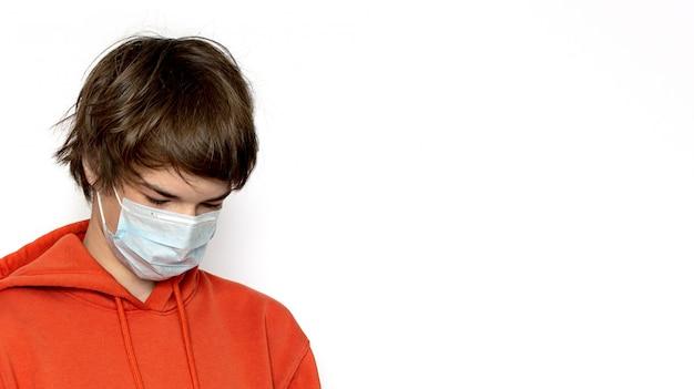 Smutny nastolatek szkolący się w domu w przestrzeni medycznej mascopy. kolor pomarańczowy. wynik pozytywny.