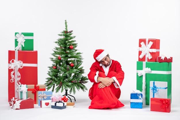 Smutny niezadowolony młody człowiek przebrany za świętego mikołaja z prezentami i zdobioną choinką siedzi na ziemi na białym tle