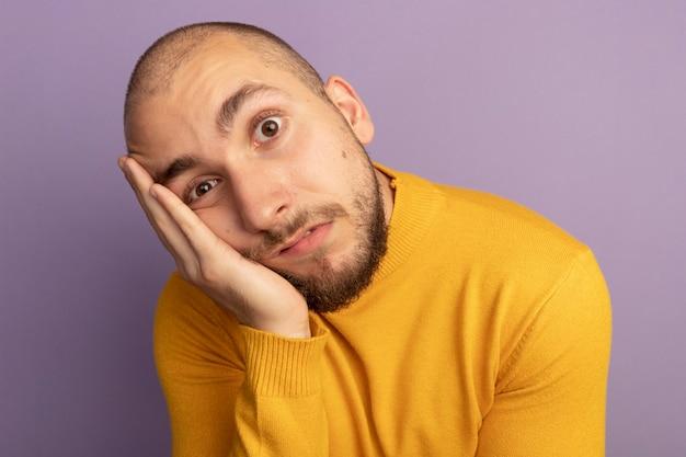 Smutny patrząc prosto przed siebie młody przystojny facet kładąc rękę na policzku na białym tle na fioletowo