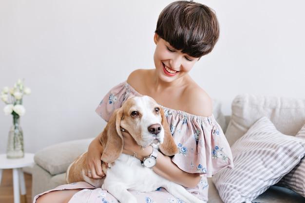 Smutny pies rasy beagle, patrząc od hotelu, podczas gdy piękna dziewczyna z uroczym uśmiechem pozowanie