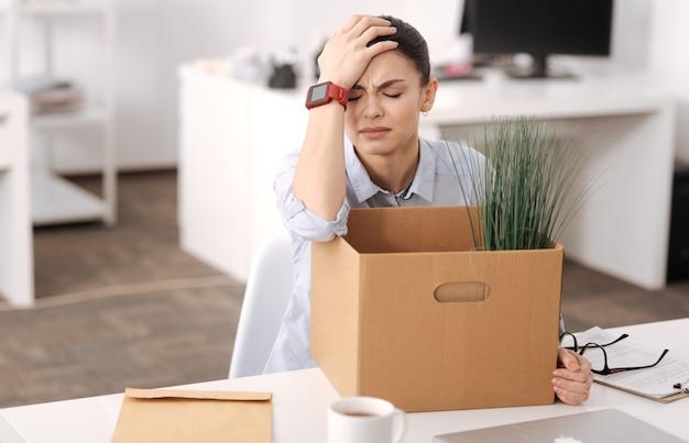 Smutny pracownik biurowy w inteligentnych zegarkach kładzie rękę na głowie i ściska usta