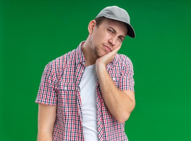 Smutny, przechylający się, młody facet sprzątacz w czapce, kładąc rękę na policzku na białym tle