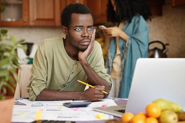 Smutny, przygnębiony ciemnoskóry mężczyzna w okularach, opierający łokieć o stół, zestresowany i zdziwiony, próbujący znaleźć rozwiązanie problemów finansowych i spłacić wszystkie rodzinne długi