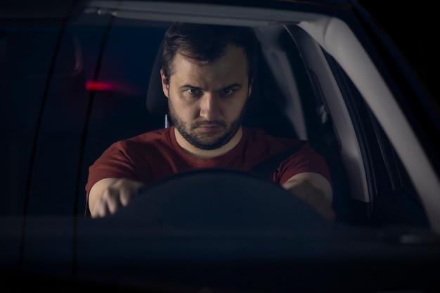 Smutny przygnębiony mężczyzna spędzający samotnie czas w samochodzie w nocy, czując się samotny