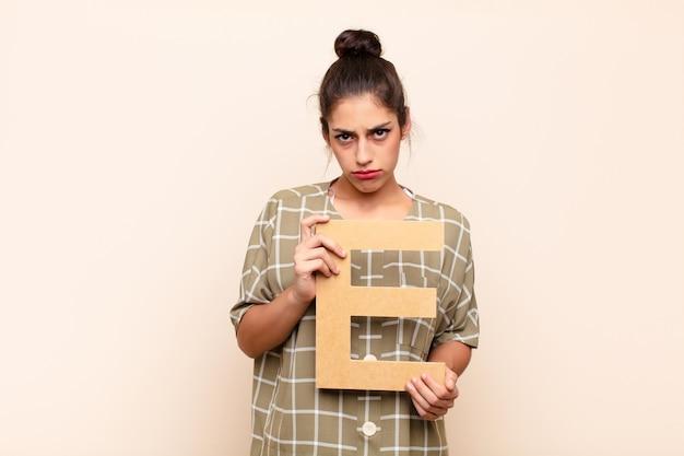 Smutny, przygnębiony, nieszczęśliwy, trzymając literę e alfabetu, aby utworzyć słowo lub zdanie.