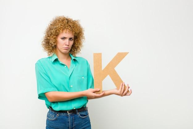 Smutny, przygnębiony, nieszczęśliwy, trzymając literę k alfabetu, aby utworzyć słowo lub zdanie.