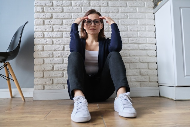 Smutny przygnębiony wiek samotna kobieta siedzi na podłodze