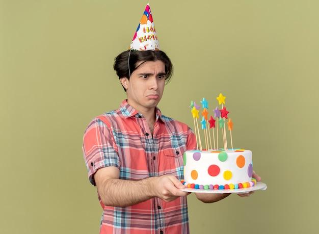 Smutny przystojny kaukaski mężczyzna w czapce urodzinowej trzyma i patrzy na tort urodzinowy