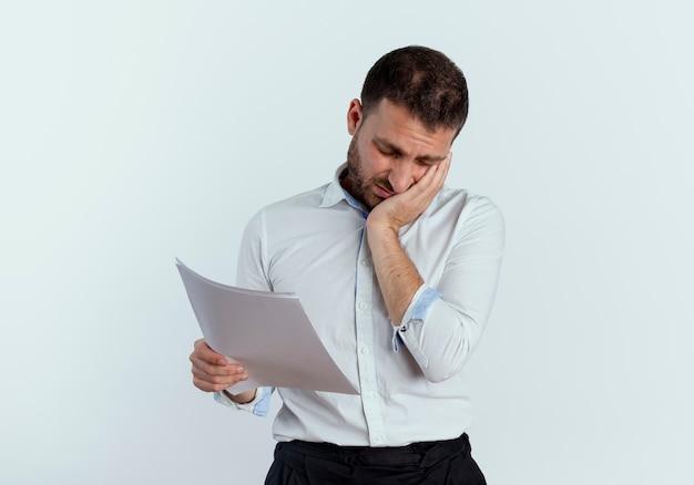 Smutny przystojny mężczyzna kładzie rękę na twarzy trzymając arkusze papieru na białym tle na białej ścianie