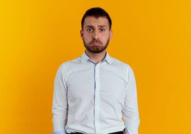 Smutny przystojny mężczyzna patrząc na białym tle na pomarańczowej ścianie