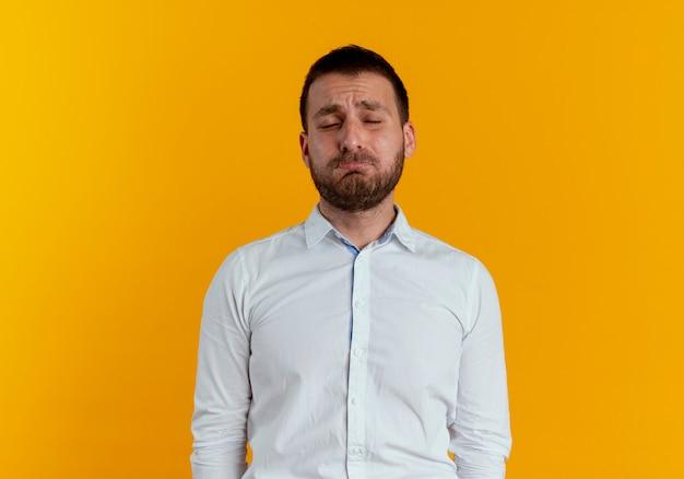 Smutny przystojny mężczyzna stoi z zamkniętymi oczami na białym tle na pomarańczowej ścianie