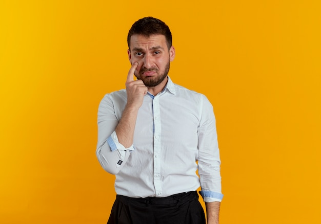 Smutny przystojny mężczyzna wskazuje na oko na białym tle na pomarańczowej ścianie