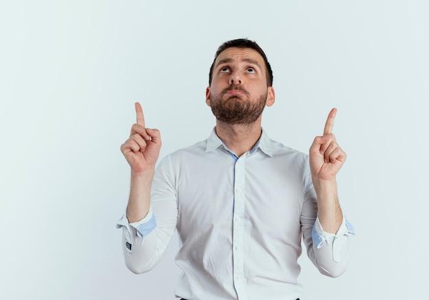 Smutny przystojny mężczyzna wygląda i wskazuje dwiema rękami na białej ścianie