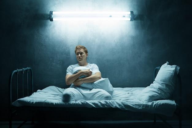 Smutny psychol mężczyzna siedzi samotnie w łóżku, ciemny pokój. osoba psychodeliczna mająca problemy każdej nocy, depresja i stres, smutek, szpital psychiatryczny