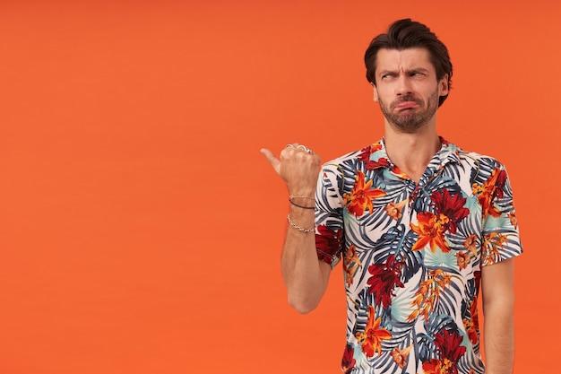 Smutny, rozczarowany młody człowiek z zarostem w hawajskiej koszuli stoi i wskazuje palcem kciuka w bok w pustą przestrzeń