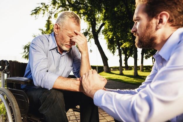 Smutny rozweselać dziadka w parku. pomoc dla niepełnosprawnych.