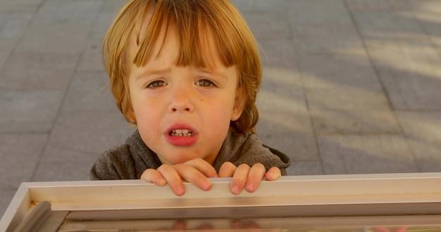 Smutny rudy chłopiec imbir patrząc na kamery